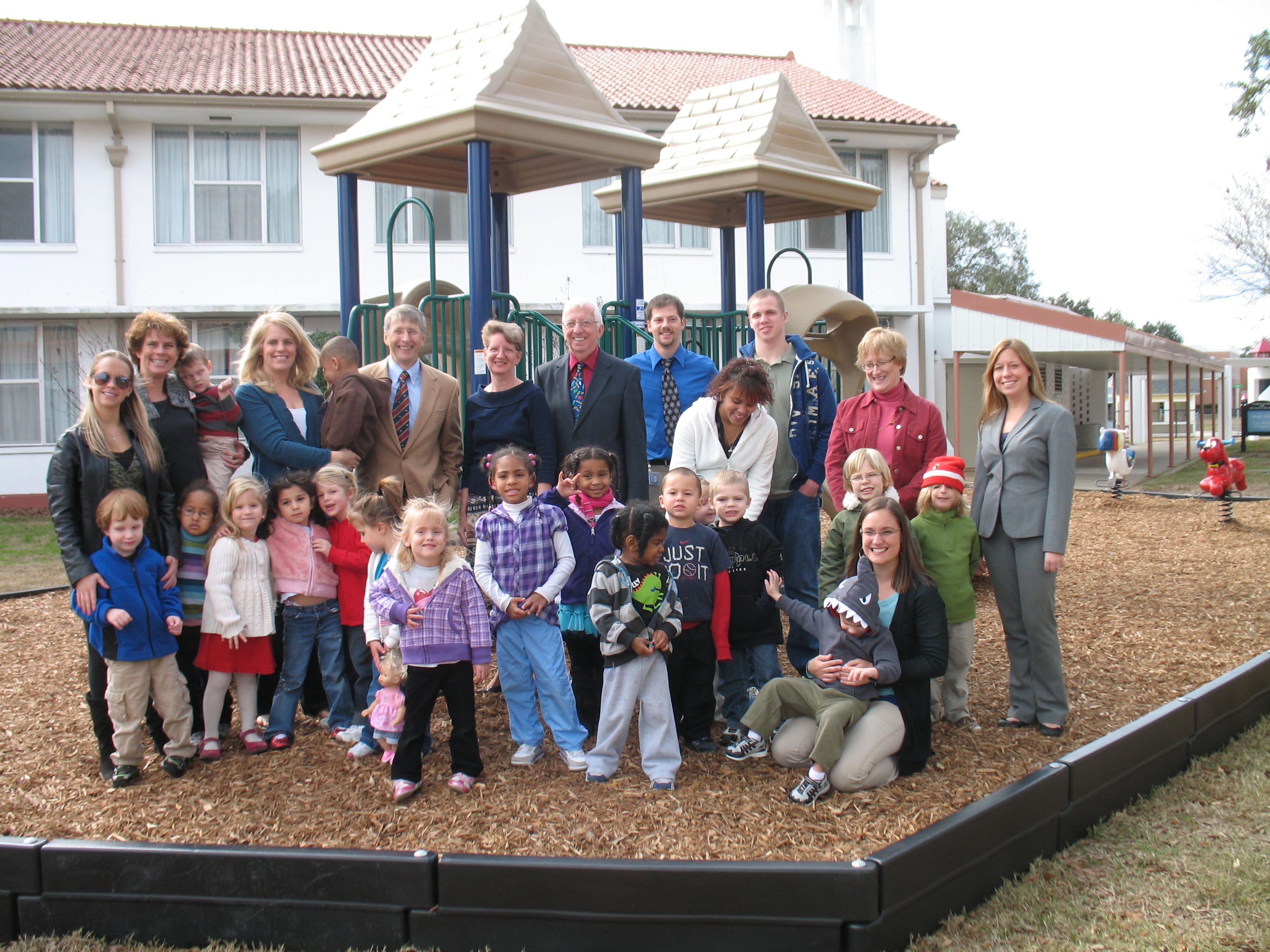 group photo of parents and children at a playground