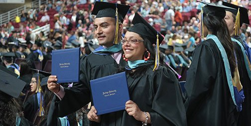 students in caps and gowns holding up their diploma