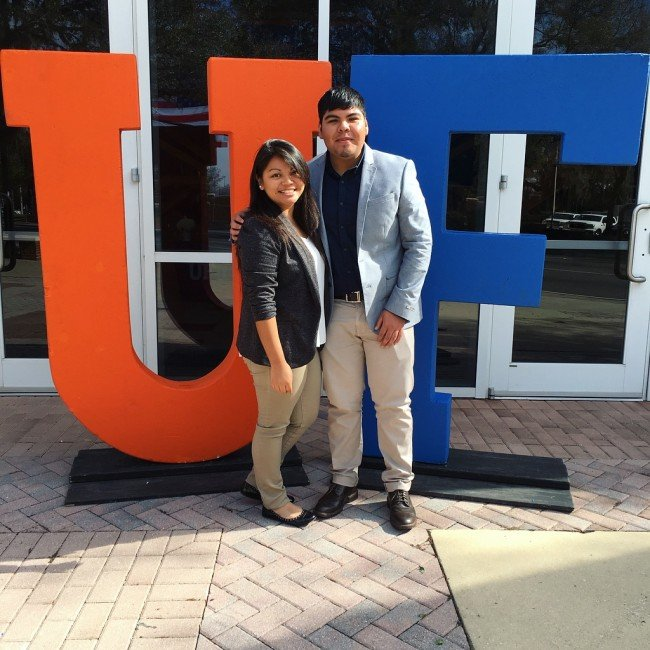 Two people posed in front of UF sign