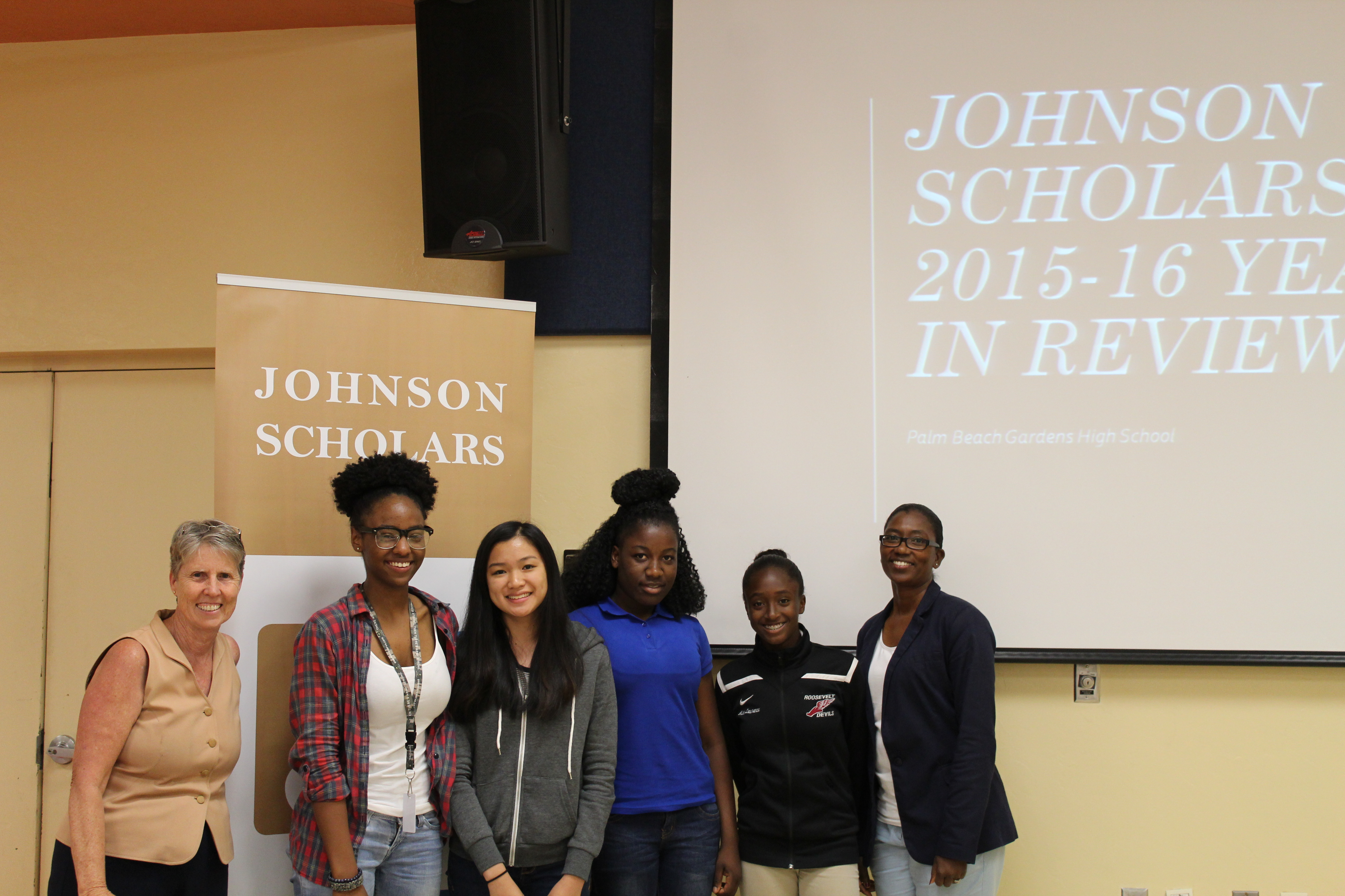 teachers and students posing in front of johnson scholars sign