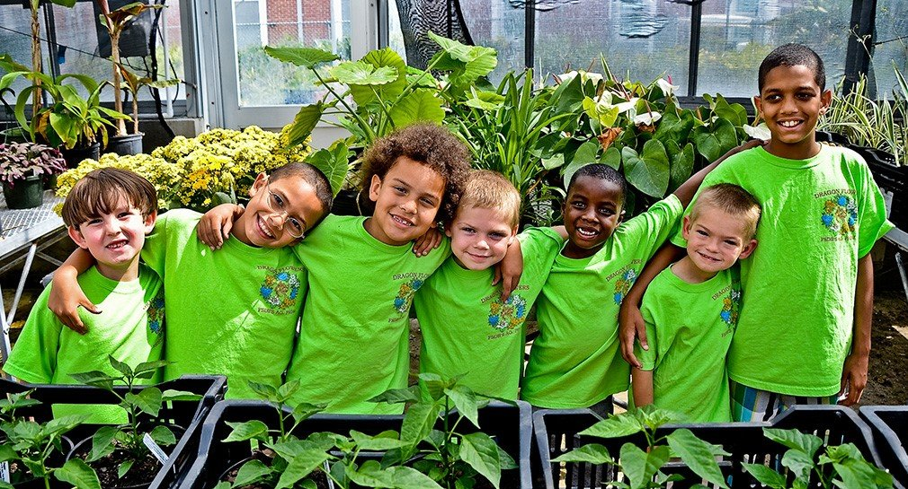 young students in green t shirts in a garden