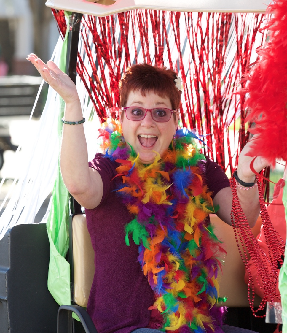 woman wearing a feather boa and smiling in a parade