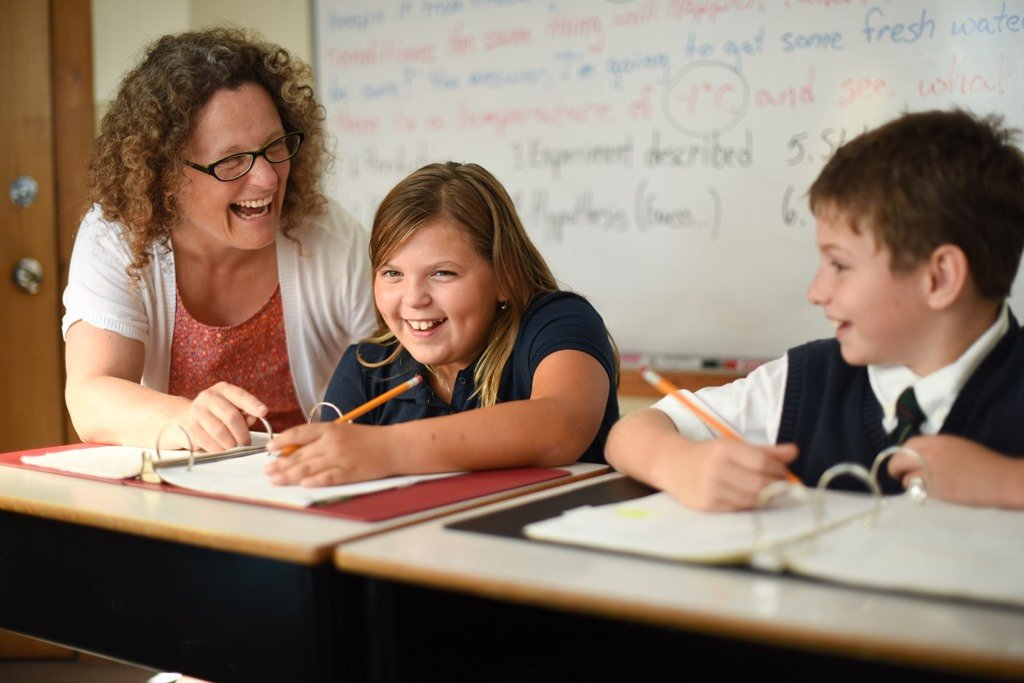 Teacher and two students working at their desks smiling
