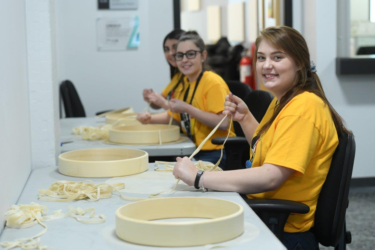 Students making drums using traditional methods