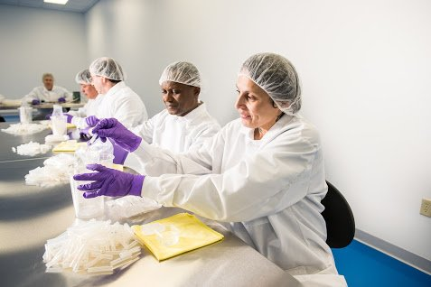 MDI employees work in a sterile room to package items such as medical supplies.