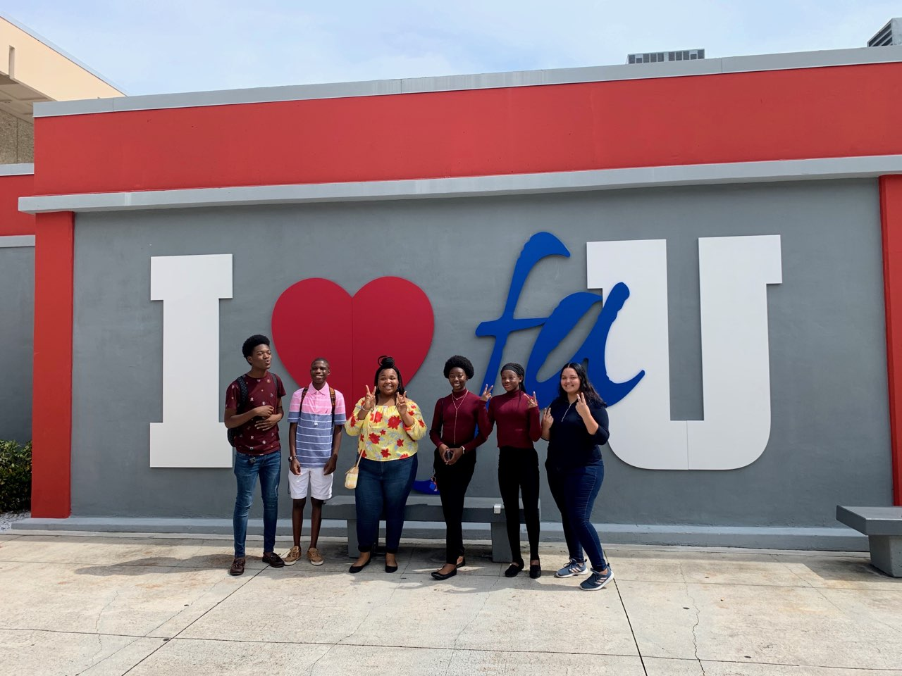 Group of 6 students in front of I love FAU sign