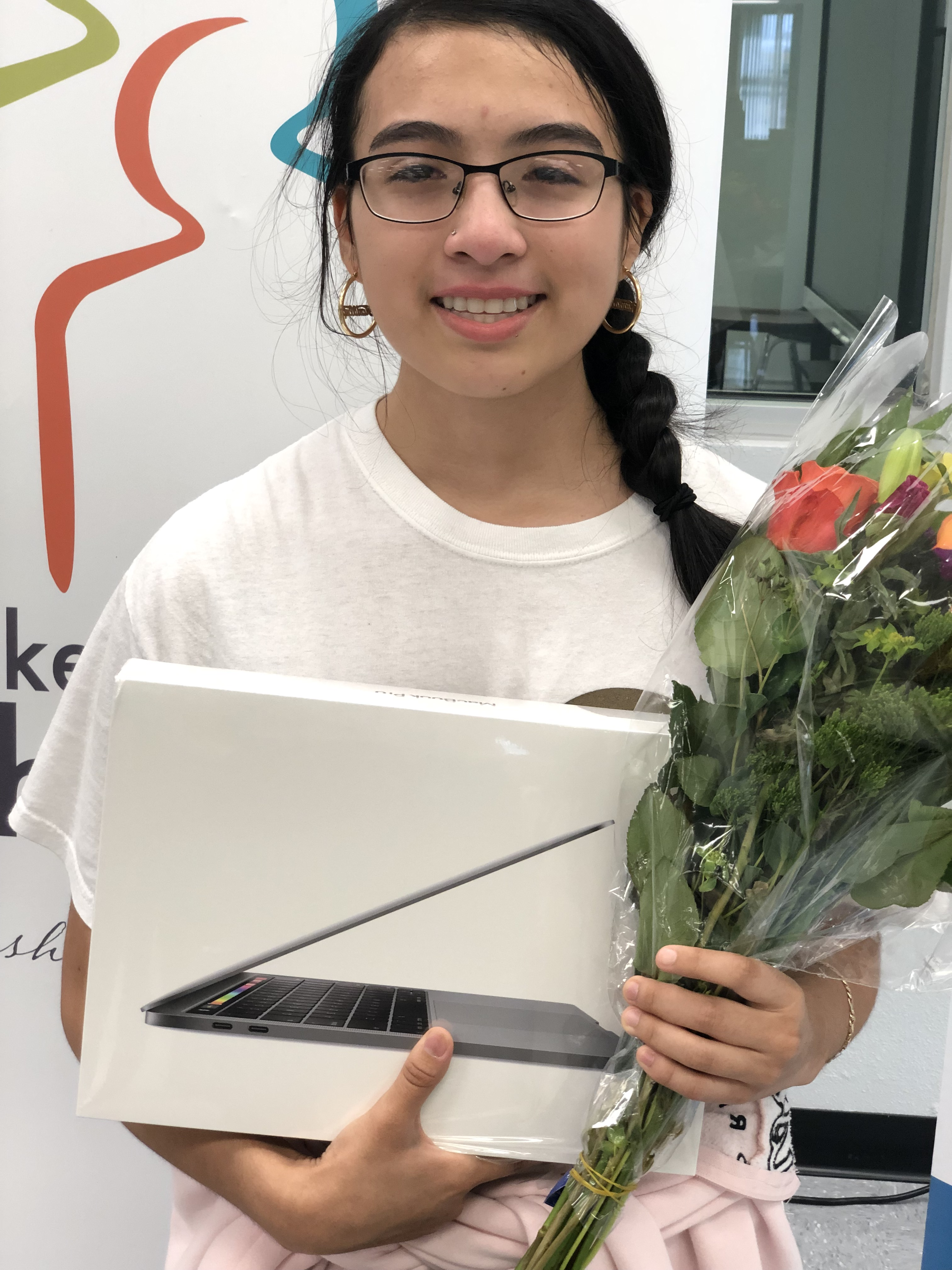 Gema Cervantes holding laptop and flowers
