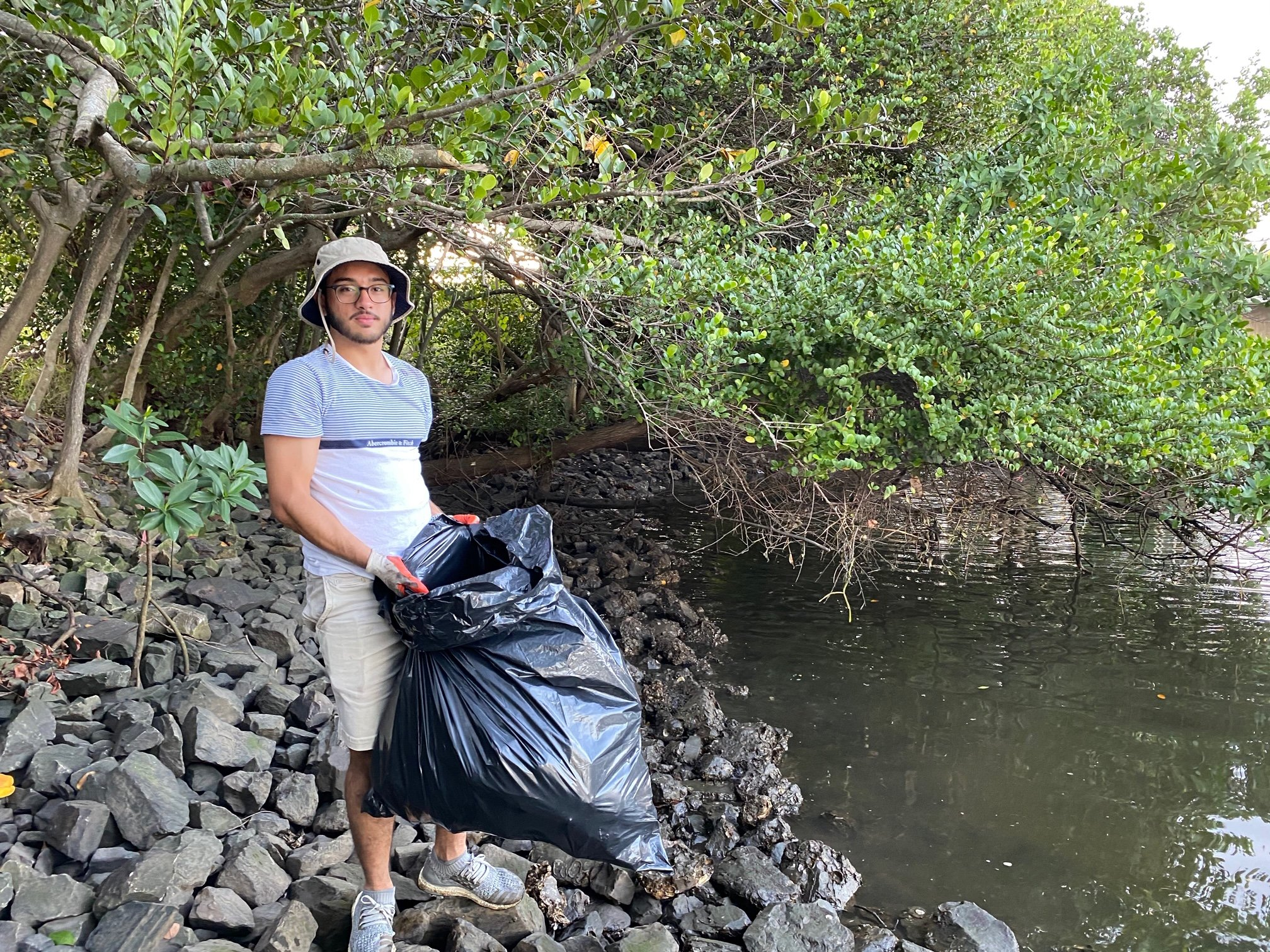 Evan Cabrera in mangroves with trash bag