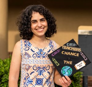"""Alex Dixon holds her graduation mortarboard bearing the words """"teachers change the world"""" and """"class of 2021."""""""